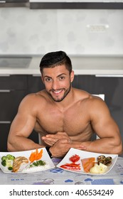 young bodybuilder in the kitchen, with two plates of healthy food: rice, chicken grill, broccoli, carrots, mushrooms, salmon, tomato, red peppers, potatoes