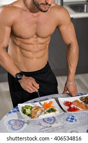 young bodybuilder in the kitchen with two plates of healthy food: rice, chicken grill, broccoli, carrots, mushrooms, salmon, tomato, red peppers