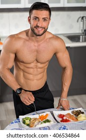 young bodybuilder in the kitchen with two plates of healthy food: rice, chicken grill, broccoli, carrots, mushrooms, salmon, tomato, red peppers, potatoes