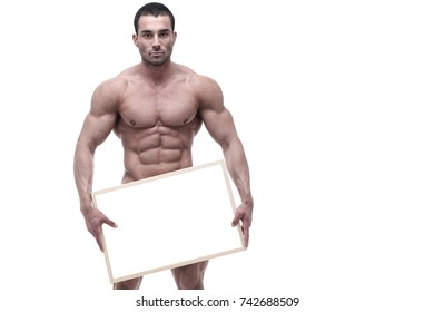 Young bodybuilder posing with white board in front of white background