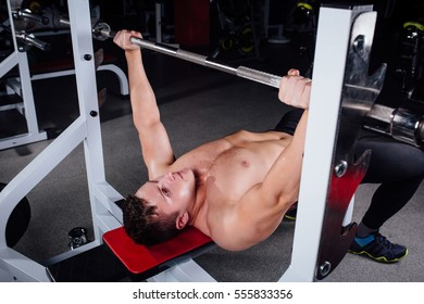 young bodybuilder training in the gym: chest - barbell incline bench press - wide grip,