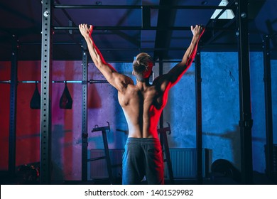 Young bodybuilder training in the gym exercising Wide-Grip Pull-Up, back view. The session covers the kipping pull-up, the butterfly pull-up and the butterfly chest-to-bar pull-up.