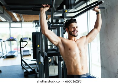 Young bodybuilder training in gym on machine