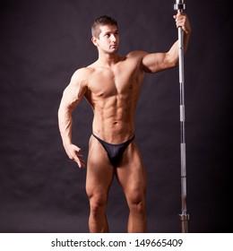 young bodybuilder traininig over balck background