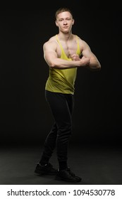 young bodybuilder in t-shirt shows off double bicep in front of on a black background