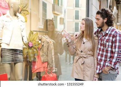 Young bohemian couple looking at clothes in a store window while on vacations in a destination city, pointing at a variety of items.