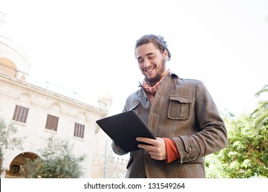 Young bohemian man using a digital tablet pad while smiling visiting an old destination city during a sunny day, on vacation.
