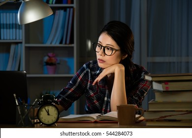 young bored female college student studying poorly at late evening before exam, funny night procrastination concept. mixed race asian chinese model.