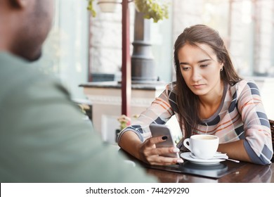 Young bored girl sitting and using smartphone on date with her boyfriend at cafe. Speed dating, unsuccessful meeting