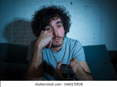Young bored man on couch using TV remote control zapping for another movie or show late at night. Looking disinterested and sleepless. In entertainment People insomnia and Sedentary lifestyle concept.