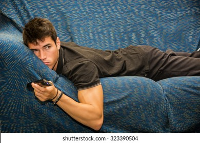 Young bored man sitting on sofa watching television changing the channel with the remote control