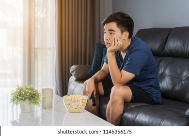 young bored man watching tv and sitting on sofa in the living room