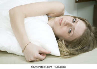 Young bored woman with lying down ot he bed over white background. Woman`s problem