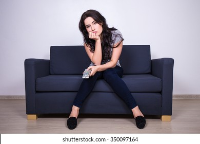 young bored woman sitting on sofa and watching tv at home