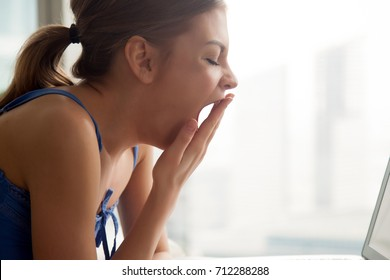 Young bored woman yawning near laptop at home covering mouth with hand, sleepy student tired of spending too much time with computer, feeling drowsy suffering from lack of sleep, side view head shot
