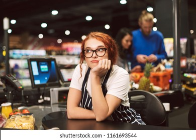 Young boring cashier in eyeglasses and striped apron dreamily looking aside working in modern supermarket with customers on background