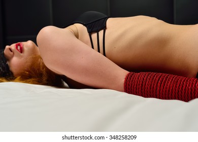 Young bounded woman on the bed