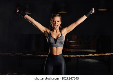 Young boxer girl with boxing gloves screams emotionally rising arms in victory sign showing fit and healthy body in female fighter and successful woman concept. Loft gym ring with ropes.
