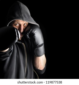 Young boxer in hood isolated on dark background