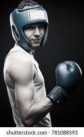 Young boxer posing over dark background