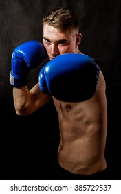 Young boxer punching right cross .Black background