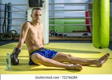 Young boxer sitting on floor after training in gym,