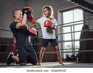 Young boxer trainer is training new girl boxer for special competitions.
