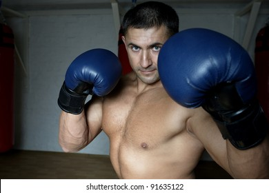 The young boxer with a well-muscled body in boxing gloves in a gym
