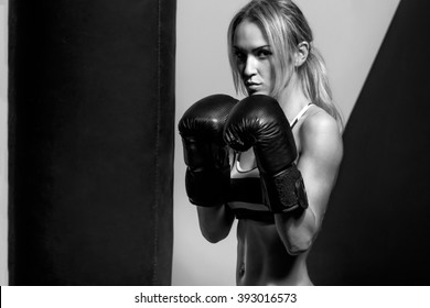 young boxer woman in boxing gloves with punching bag , on black and yellow background, black-and-white horizontal photo