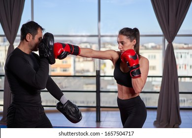 Young boxer woman hitting mitts with her coach