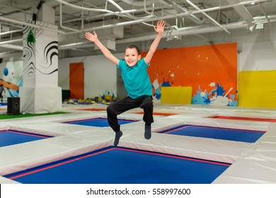 Young Boy 6 year old Jumping on a trampoline in children fitness gym