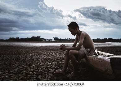 Young boy asian children anxiety to the shortage of water the effects of drought rain delay. Drought from the effects of the seasonal rain.