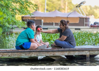 A young boy is asking to share his mother's watermelon while sitting on a dock
