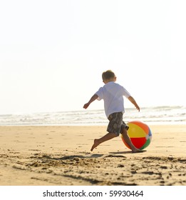 Young boy at the beach plays with a big beachball