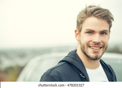 Young boy with beard on smiling handsome sexy face blue eyes brown hair in dark blue hoody posing on gray car background outdoor