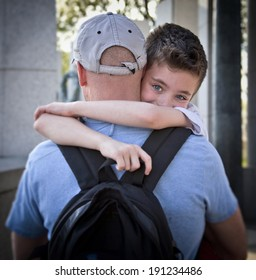 Young boy being carried by father in an embrace