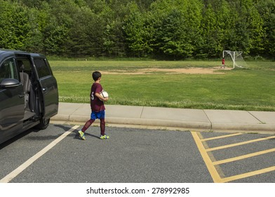 A young boy being dropped off for soccer practice. Spring setting, horizontal composition.
