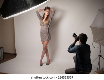 Young boy, bent knees, photographing a model on a set