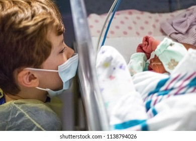 Young boy big brother wearing face mask and gown while looking at his newborn sister at a hospital nursery