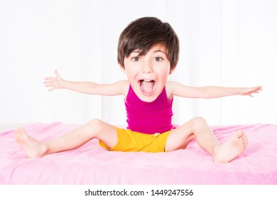 young boy with big head sitting in bed on a pink blanket and laughing