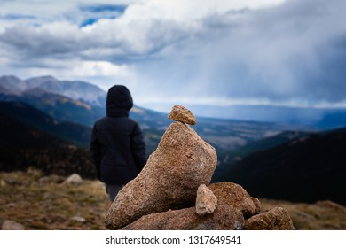 young boy in black jacket stands behind pile of rocks taking in a scenic mountain view