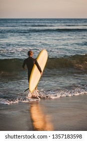 Young boy in black wetsuit carries his white and yellow surfboard out to catch some waves in the Pacific Ocean in Malibu, California.