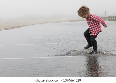 A young boy with blonde curly hair and a red plaid shirt is jumping in a large puddle after a big rainstorm in the spring season. He is splashing in the water with his rain boots. The boy is wet