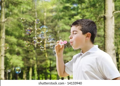 Young boy blowing bubbles in park. Copy space