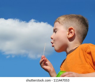A young boy is blowing bubbles and there is a white cloud on a blue sky to add your text message. Use it for a fun summer concept.