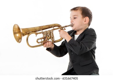 young boy blowing into a trumpet against white background