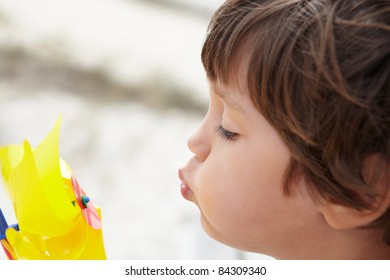 Young boy blowing on windmill
