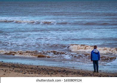 A young boy in a blue coat and tracksuit looking out to the North Sea as a foamy wave breaks on the beach at Cromer, Norfolk, UK in the winter.