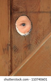 Young boy with blue eyes peeking through a hole in a fence.