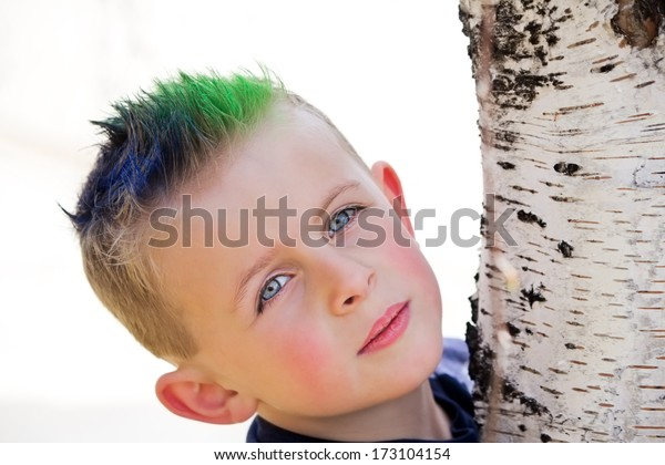 Young boy with blue and green spiky hair hugging birch tree trunk